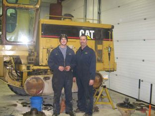 two men in front of machinery